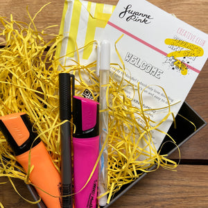 Doodler's Art Set with orange and pink highlighters, white gel pen and fineliner nestled in yellow recycled shredded paper.