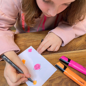 Child using fineliner to add details to orange and pink highlighter doodles.