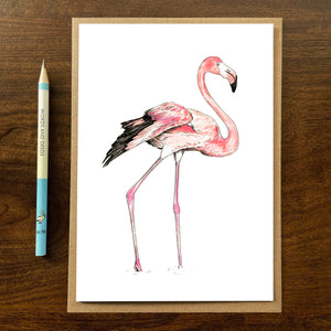 Flamingo greetings card with kraft envelope on wooden background with pencil.