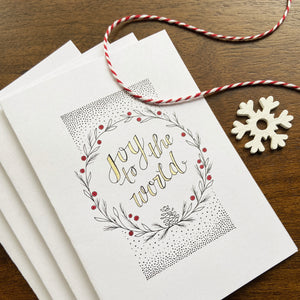 Joy to the World wreath card with festive twine and wooden snowflake charm.