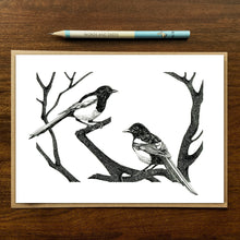 Load image into Gallery viewer, magpies greetings card on wood background with recycled kraft envelope and pencil.