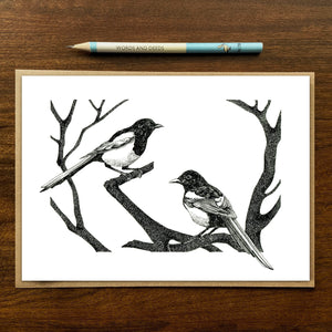 magpies greetings card on wood background with recycled kraft envelope and pencil.
