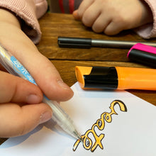 Load image into Gallery viewer, Child using fineliner to add details to orange and pink highlighter doodles.
