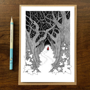 Red Riding Hood greetings card on wooden background with recycled kraft envelope and pencil.