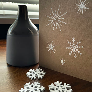 White snowflake design kraft Christmas card with wooden snowflake charms.