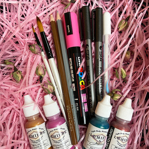 Spring Art Set materials including metalllic and pearlescent acrylic paints, paintbrushes, metallic pencils, pink posca pen and white gel pen. Nestled in pink shredded paper and dried rose buds.