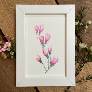 Pink blossom painting in white frame with delicate waxflowers on a wooden background.