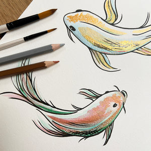 Metallic painted koi with black brush pen outlines alongside metallic pencils and paintbrushes.