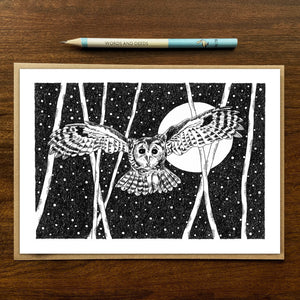 Swooping owl greetings card on wooden background with recycled kraft envelope and pencil.