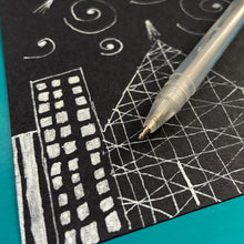 Load image into Gallery viewer, White gel pen with doodles on black paper.