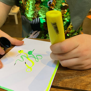 Child using yellow highlighter to doodle.