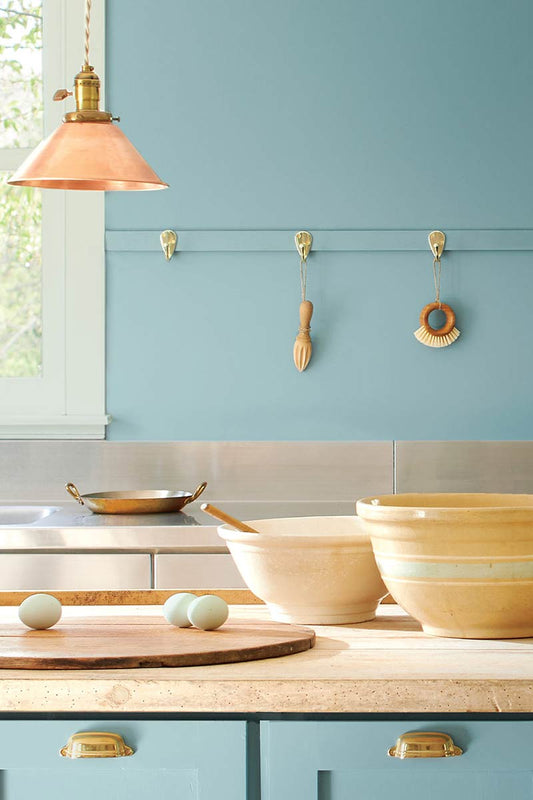 kitchen island with bowls and fruit on it, as well as blue cabinetry and walls