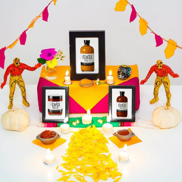Playful shrine of Filfil with colorful banners, figurines, and our delicious gourmet garlic condiments
