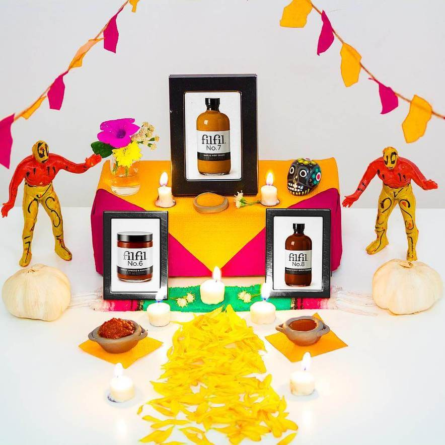 Candle lit shrine to Filfil's gourmet garlic condiments including relics, banners, and idols