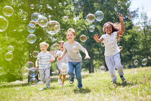 Kids playing outdoors with bubbles