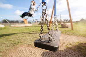 playground swing with child swinging in background