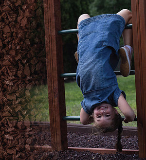 girl hanging upside down on a playset over rubber mulch