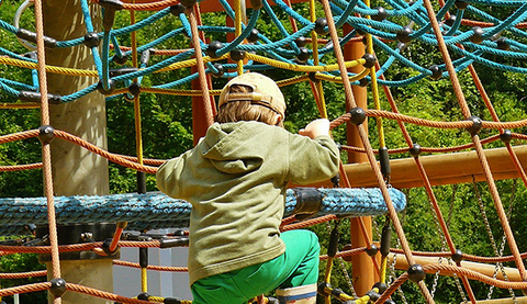 kid playing on climbing net by a playground