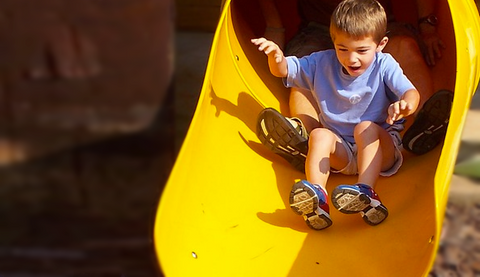 two children sliding happily down a slide