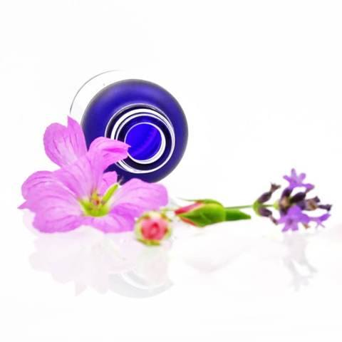 Purple glass OV naturals skincare bottle with flowers.