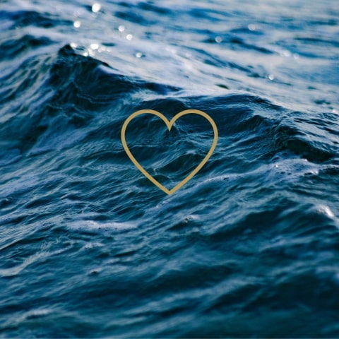 Gold heart over ocean.