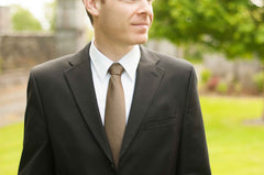Groom wearing a Antique Bronze tie and black suit