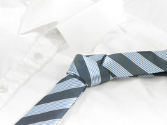 Striped air force blue and baby blue tie laying on white shirt
