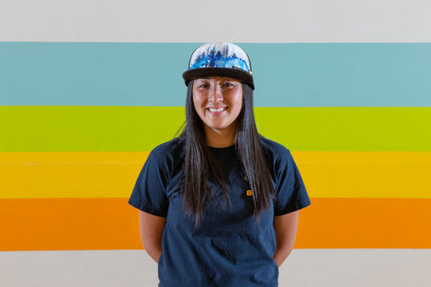 A woman with long dark hair, a hat, and a blue t-shirt smiles at the camera.