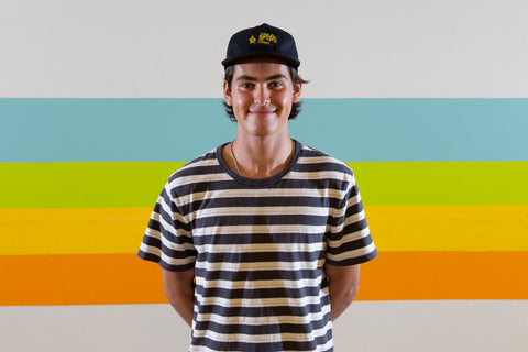 A young man in a hat and striped t-shirt smiles at the camera