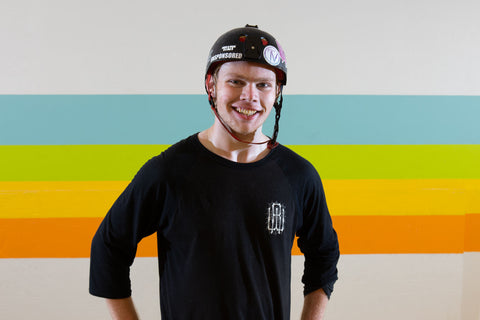 A young man in a black helmet, adorned with stickers, is smiling at the camera. He is wearing a long sleeve black t-shirt.