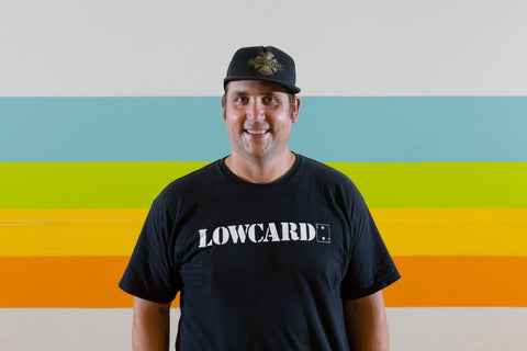 A man in an independent hat and a black lowcard t-shirt smiles at the camera