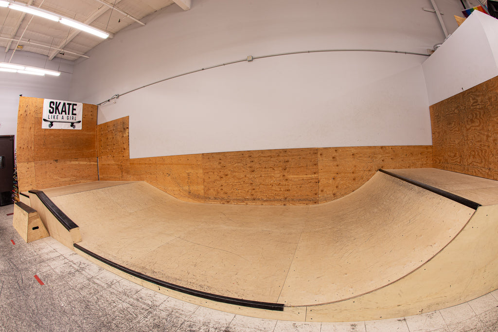 Indoor skate ramps. A small banked ramp on the left and a small quarter pipe on the right.