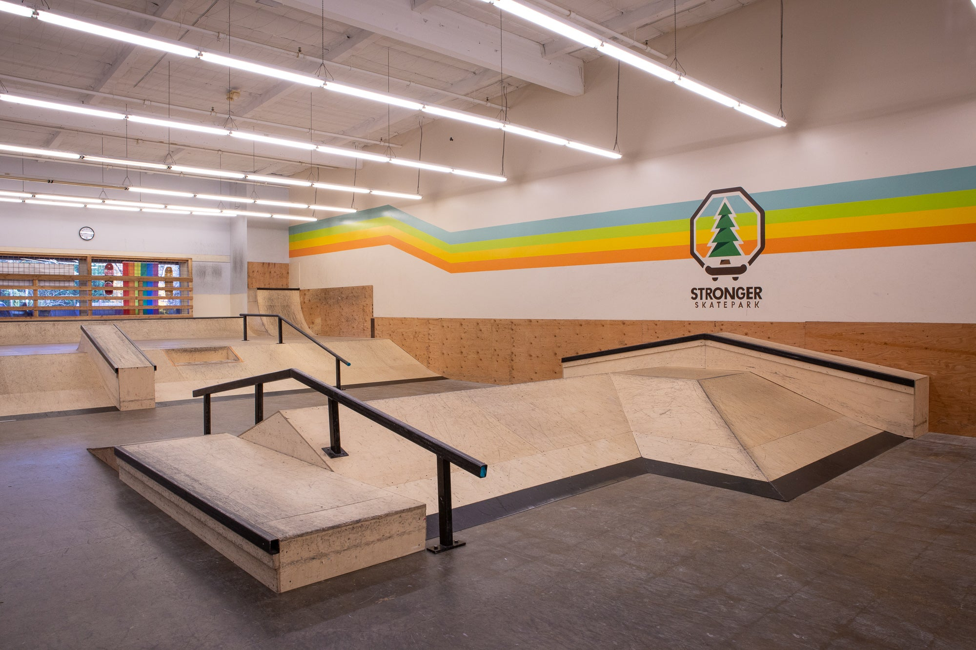 "Skatepark with ramps and rails. Mural on the wall saying ""Stronger Skatepark"" with colorful stripes running the length of the wall."