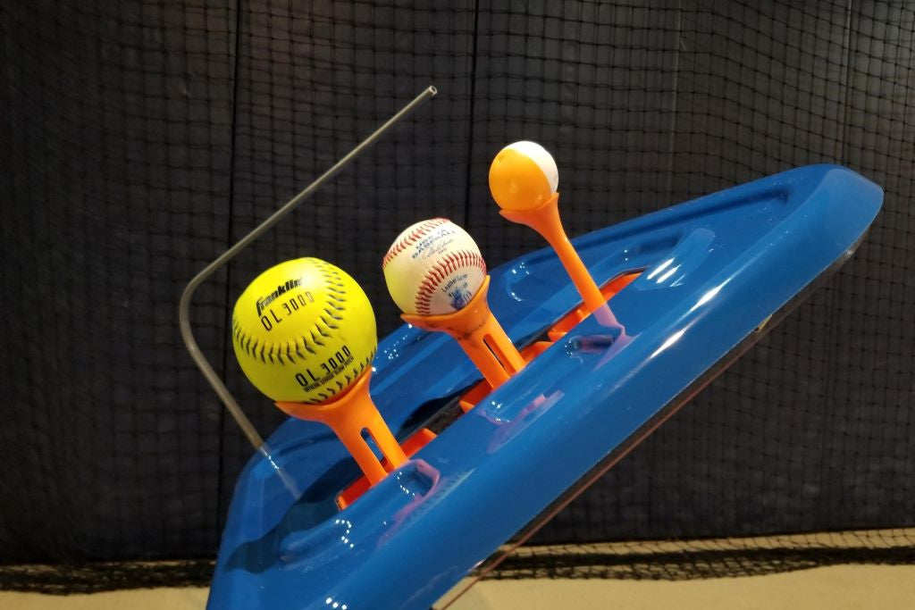 3 baseballs sitting on swing path trainer tee toppers