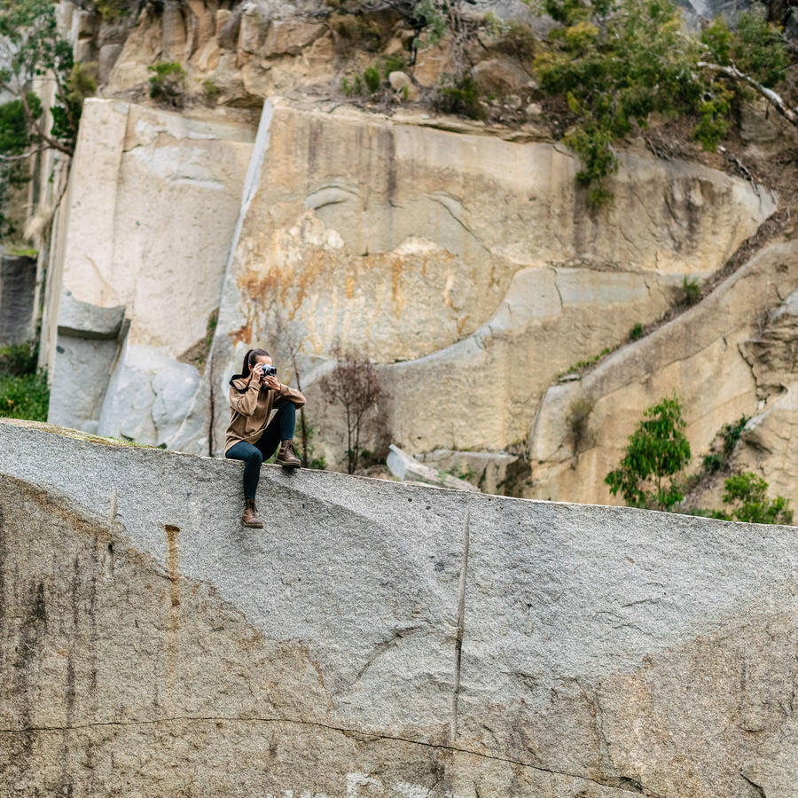 Female Photographer on Cliff using Quick Release Camera Strap