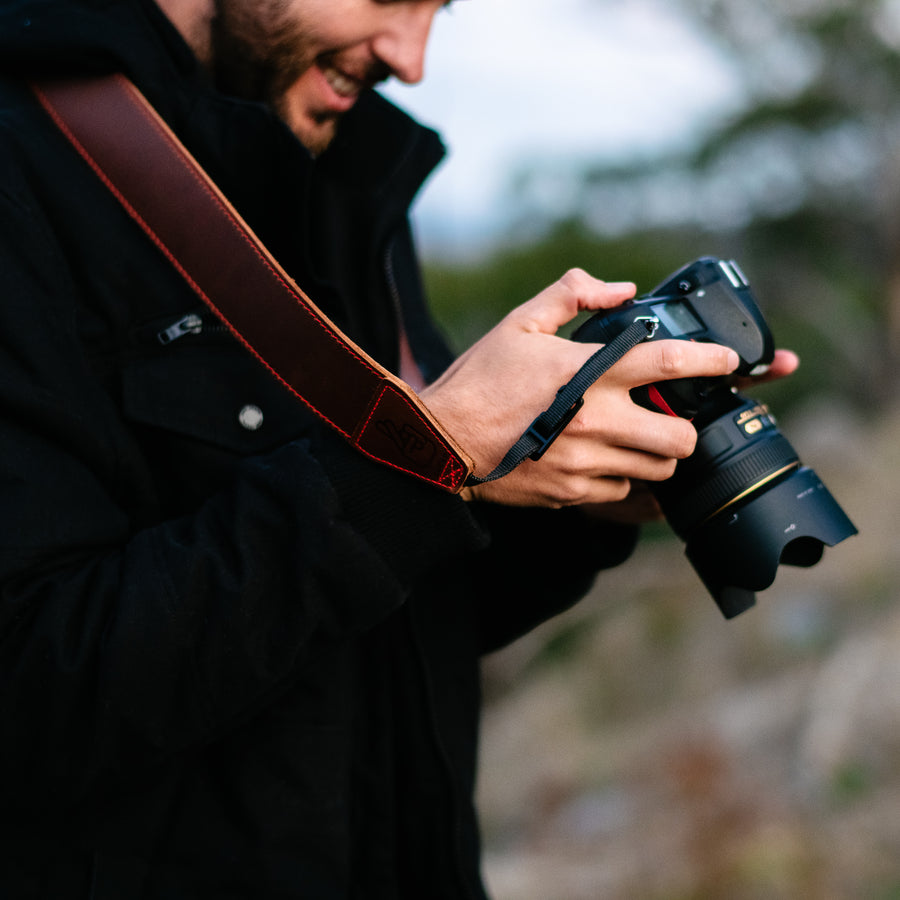 Photographer using leather camera strap which makes a great gift