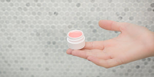 Lip Balms and Salves image featuring a pot of lip balm and a hand