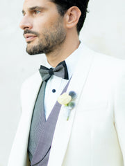 italian groom in white suit and black bow tie