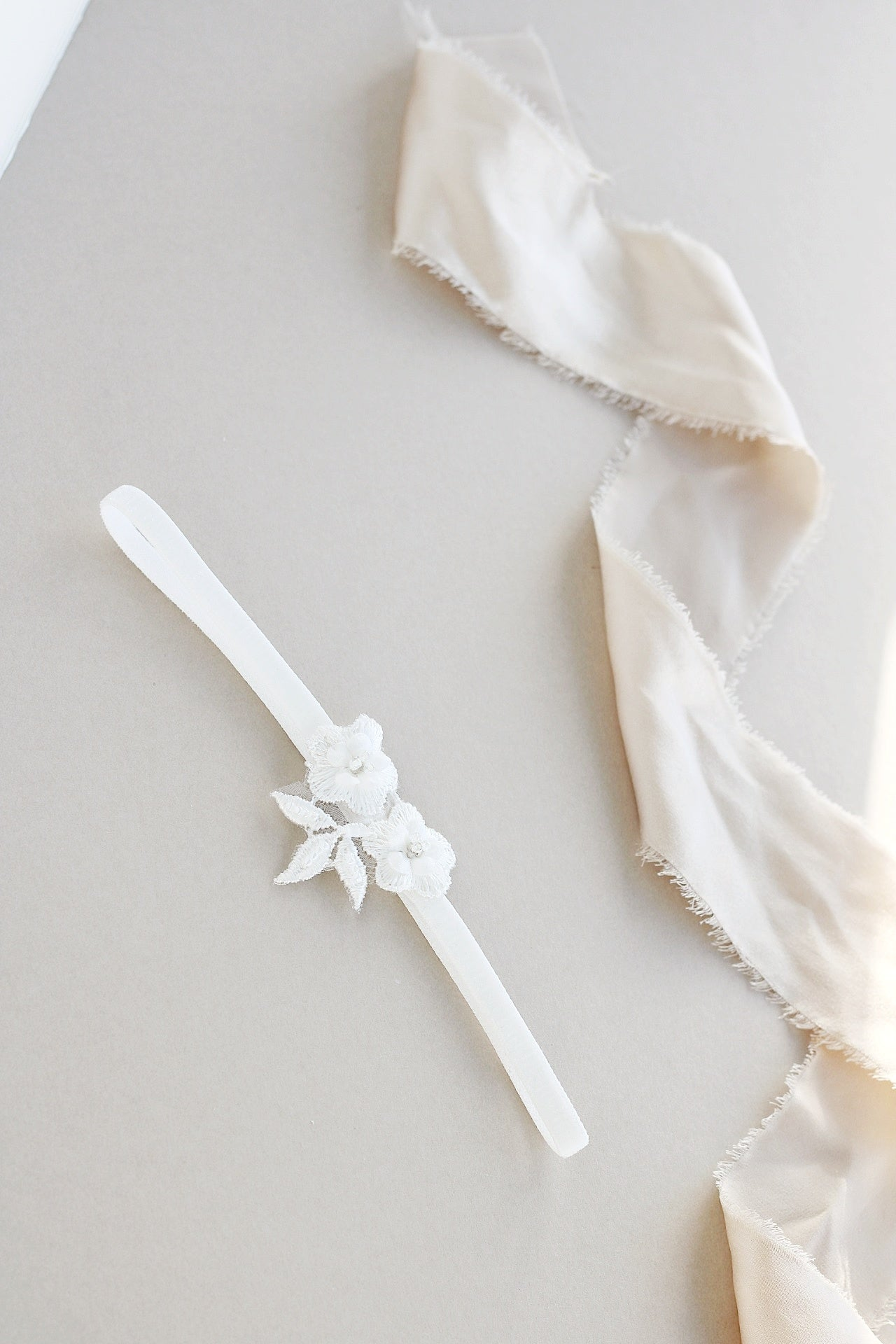 Slim velvet ivory garter with lace on table