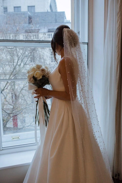classic bride wearing ivory pearl veil