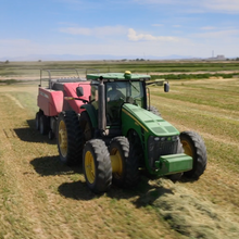 Load image into Gallery viewer, Tractor harvesting alfalfa from an alfalfa field.