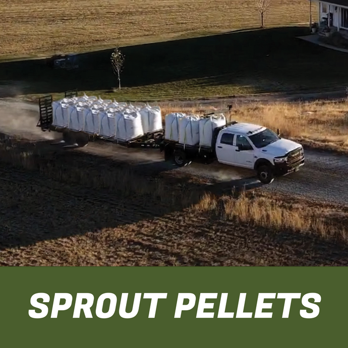 Truck pulling a trailer full of super sacks of premium horse feed pellets on a dirt road by a field..