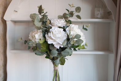 White roses, hydrangea and eucalyptus silk flower tied arrangement.