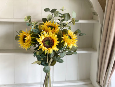 Sunflowers and eucalyptus silk flower tied arrangement.