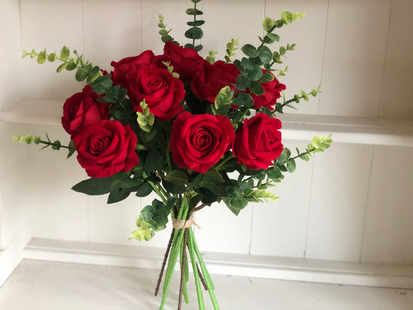 Red roses and eucalyptus silk flower tied arrangement.