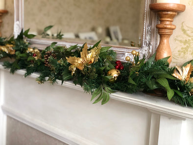 Christmas gold artificial garland. Spruce, ruscus and poinsettia