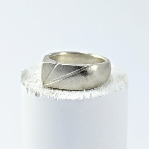 A chunky silver ring by Buster Collins. This ring has a peak at the top, with two diagonal lines either side.