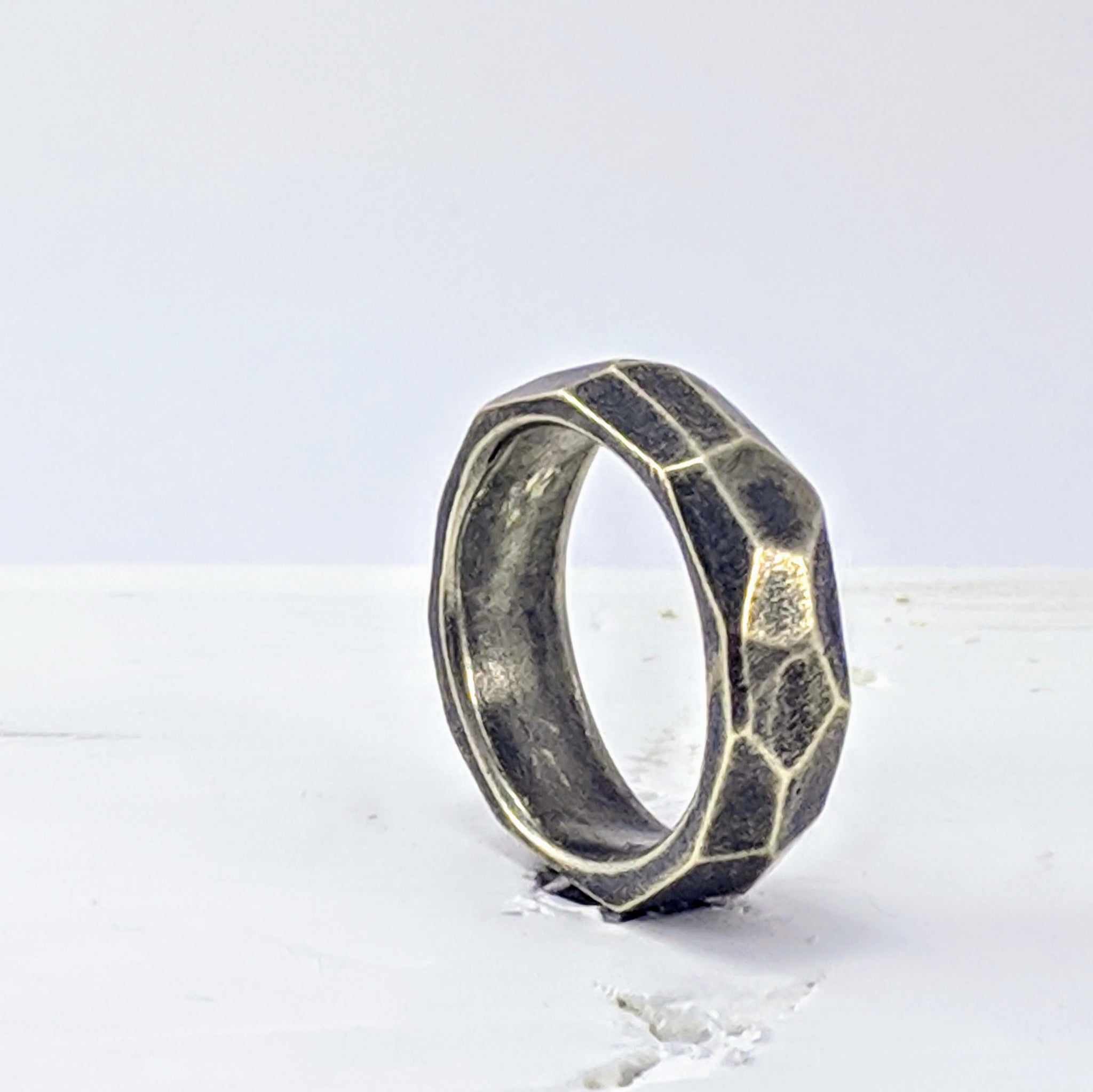 Handmade in New Zealand, this is a chunky silver ring with facets hand carved in wax and cast. by Buster Collins