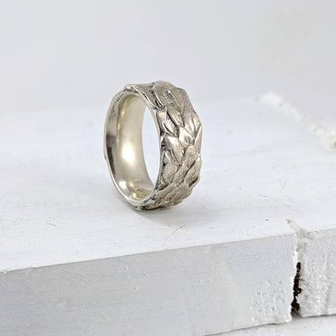 A chunky solid silver ring carved around the band with small feathers. The inside of the ring is smooth and curved. Handmade in NZ by The Wild Jewellery.