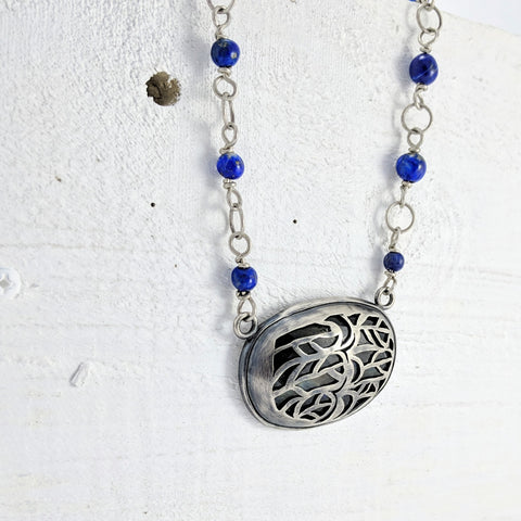 Unique jewellery handmade in New Zealand by Vaune Mason. This silver necklace is set with a large labradorite stone with swan and feather designs cut out. The silver chain is handmade in a rosary style and strung with Lapis beads.